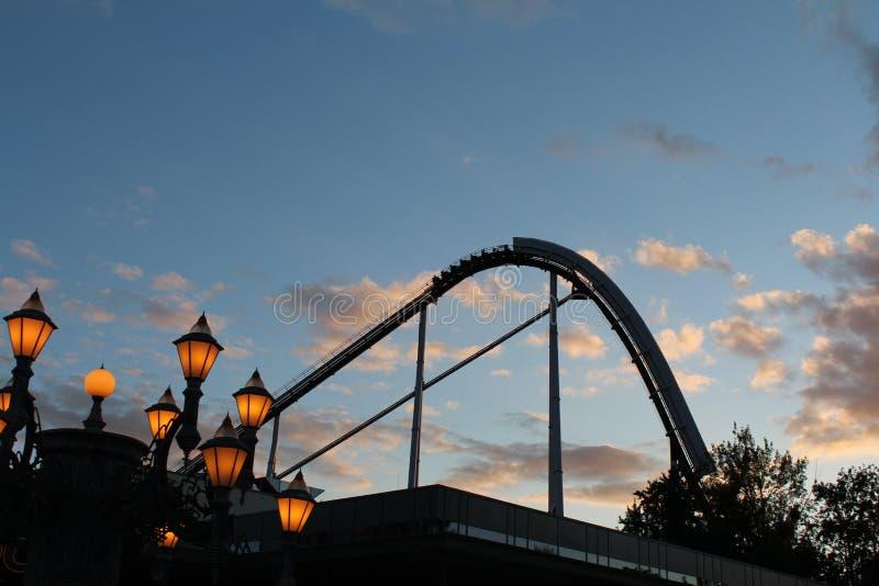 Siluetta delle montagne russe nel cielo blu all'alba fotografia stock libera da diritti