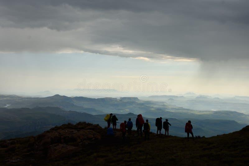 Siluetta delle viandanti che esaminano le montagne e le valli fotografia stock libera da diritti