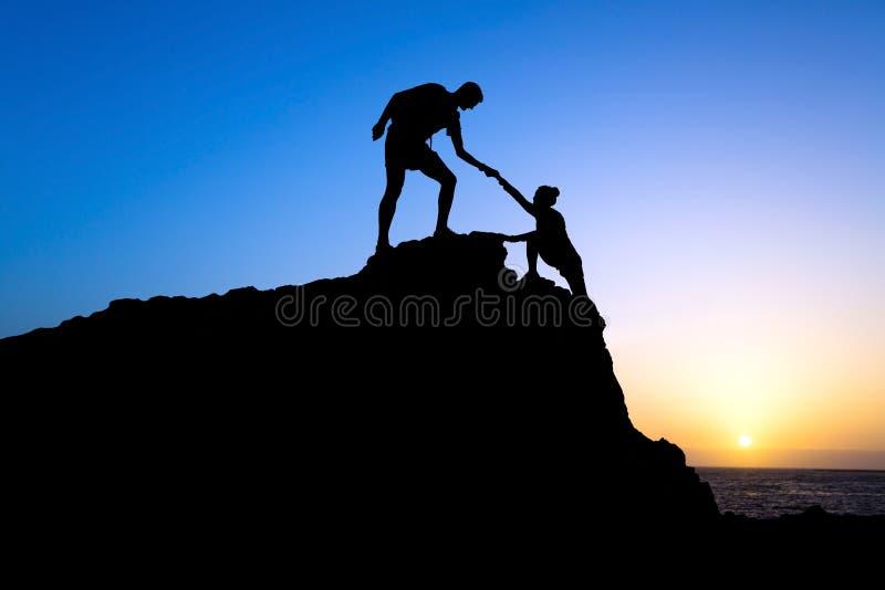 Siluetta di aiuto della donna e dell'uomo in montagne immagini stock libere da diritti