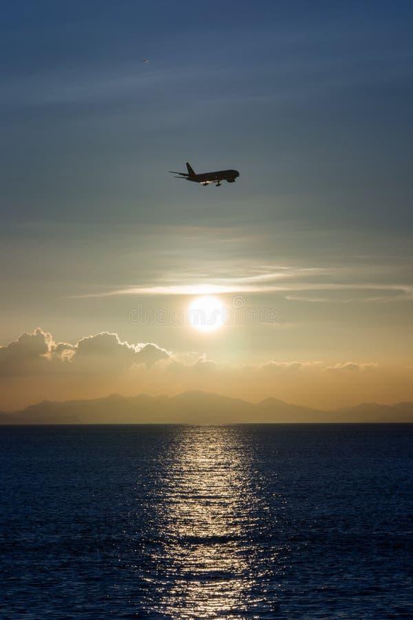 Siluetta di atterraggio di aeroplano nel tramonto fotografia stock libera da diritti