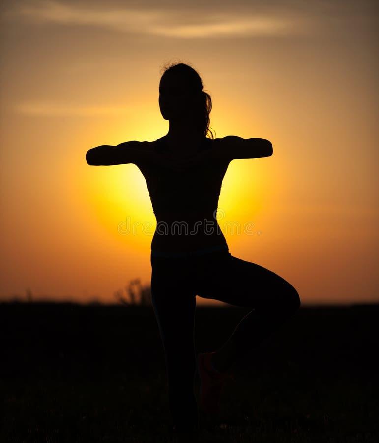 Siluetta di bella donna di yoga di mattina fotografia stock