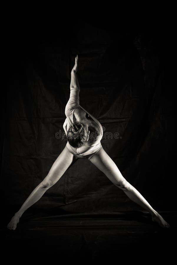 Siluetta di bella giovane donna nella posa di dancing su fondo nero immagini stock