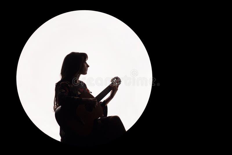 Siluetta di bella ragazza castana che gioca chitarra Concetto per le notizie di musica Copi lo spazio Cerchio bianco come la luna immagine stock