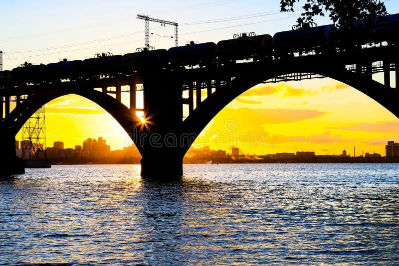 Siluetta di bello ponte ferroviario incurvato e dei vagoni sul fiume di Dnieper al tramonto Dnipropetrovsk immagine stock