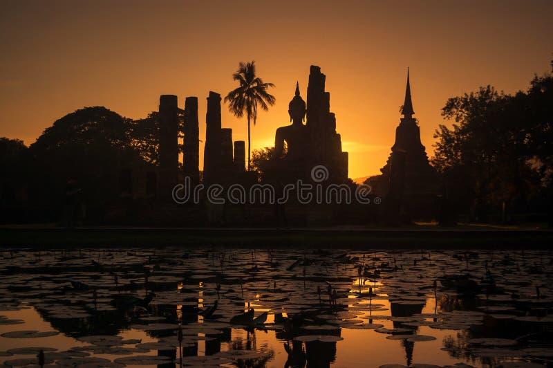 Siluetta di Buddha e pagoda su tempo di tramonto al parco di storia di Sukhothai, Tailandia Concetto di turismo della Tailandia fotografia stock