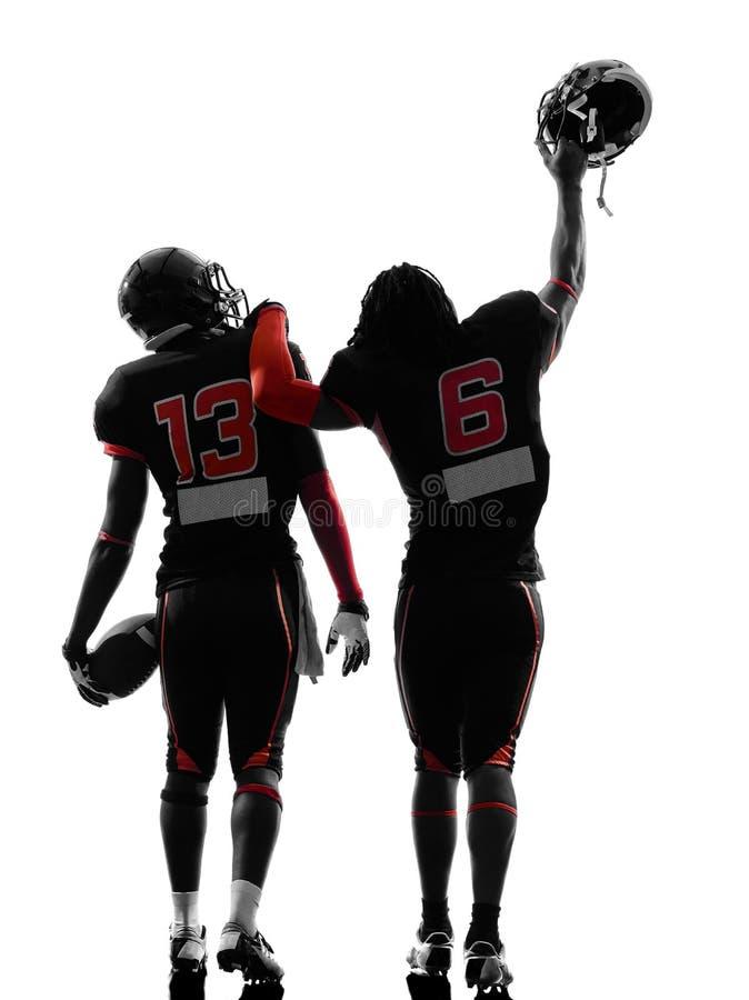 Siluetta di camminata di retrovisione di due giocatori di football americano immagini stock
