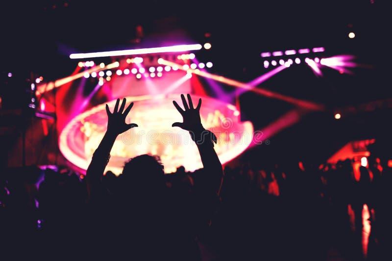 Siluetta di dancing della ragazza Concerto o festival di musica in tensione con il dancing della folla alle luci fotografia stock