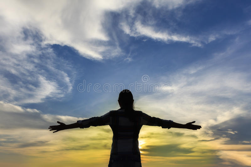 Siluetta di forte donna di fiducia a braccia aperte sotto i sunris fotografie stock