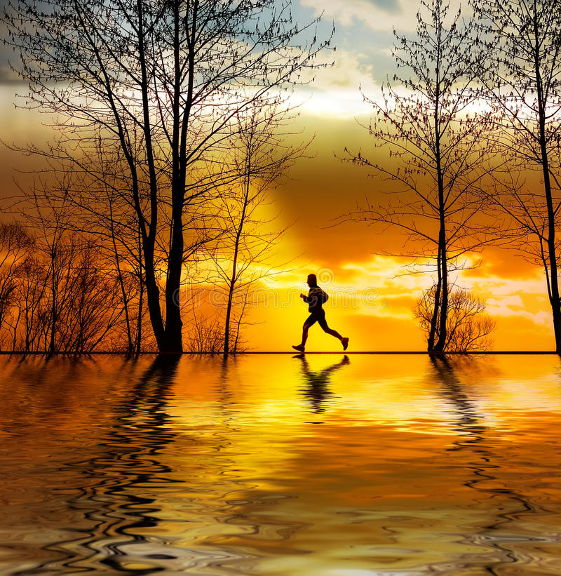 Siluetta di funzionamento dell'uomo al tramonto immagine stock