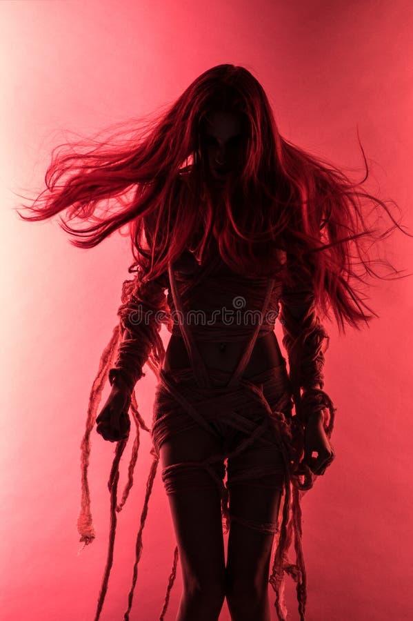 Siluetta di giovane donna della mummia in fasciatura fotografia stock