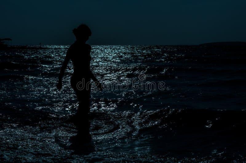 Siluetta di giovane, donna esile e sexy che cammina nel mare nell'ambito della luce della luna immagine stock