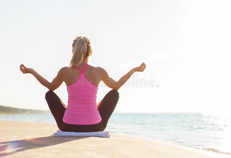 Siluetta di giovane yoga di pratica della donna in buona salute ed adatta fotografie stock