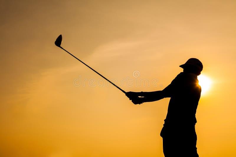 Siluetta di golf dell'azionamento del giocatore di golf con fondo arancio immagine stock