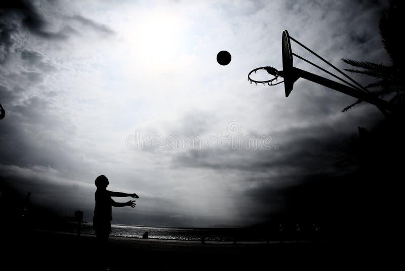 Siluetta di pallacanestro nel tramonto fotografie stock libere da diritti