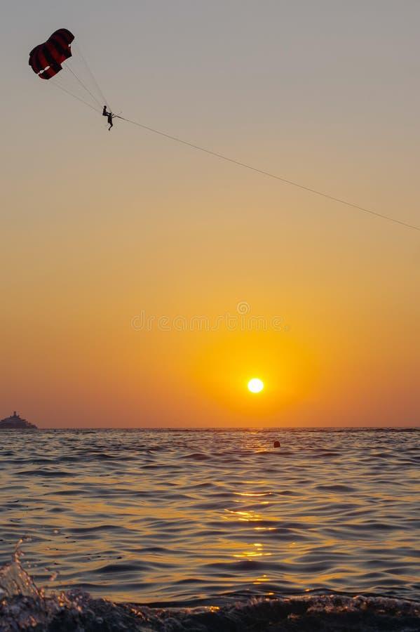 Siluetta di Parasailing in bello cielo sopra l'oceano dell'acqua di mare al tramonto arancio e rosso, isola di Phuket, Tailandia immagini stock