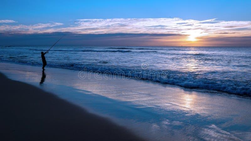 Siluetta di pesca dell'uomo sulla riva di mare con la barretta fotografia stock