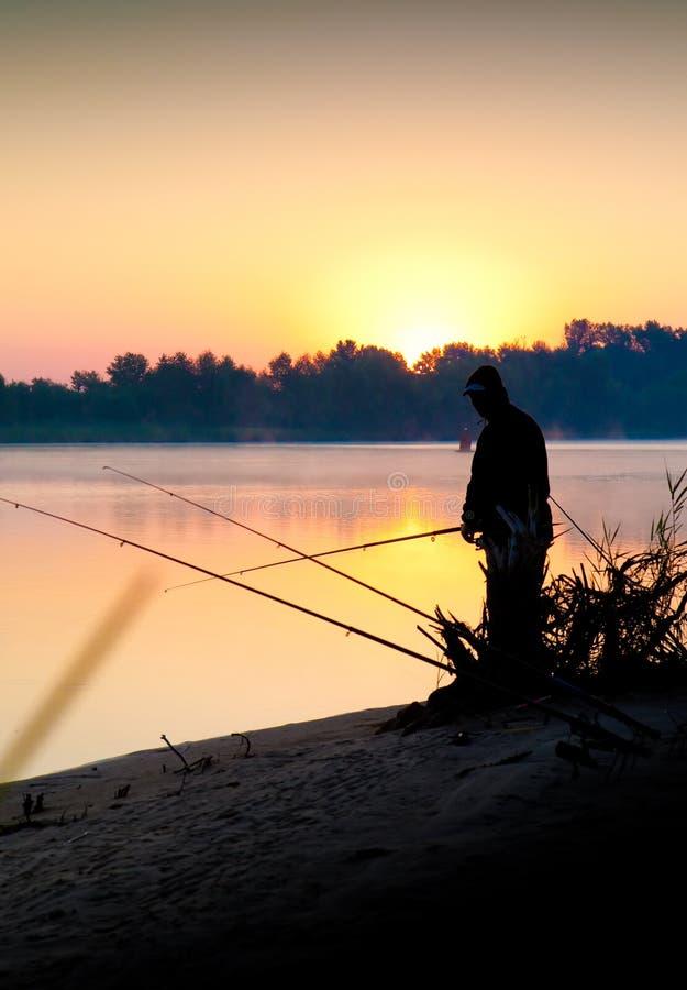 Siluetta di pesca dell'uomo in un tramonto fotografie stock libere da diritti