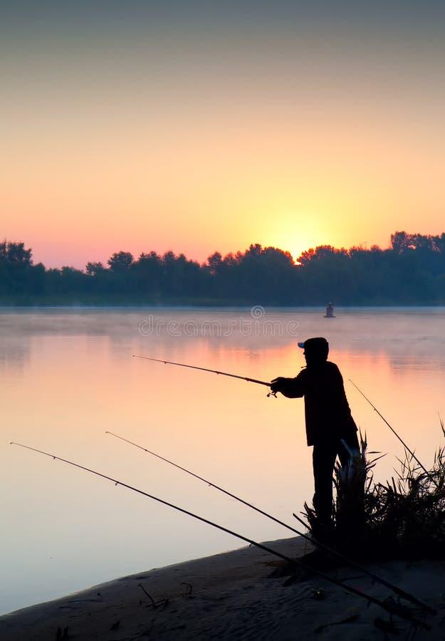 Siluetta di pesca dell'uomo in un tramonto immagini stock libere da diritti