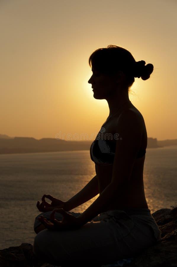 Siluetta di posa di yoga ad alba immagine stock