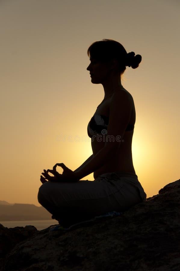 Siluetta di posa di yoga ad alba immagini stock