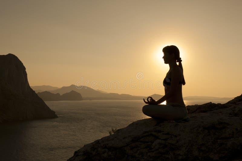 Siluetta di posa di yoga ad alba fotografia stock