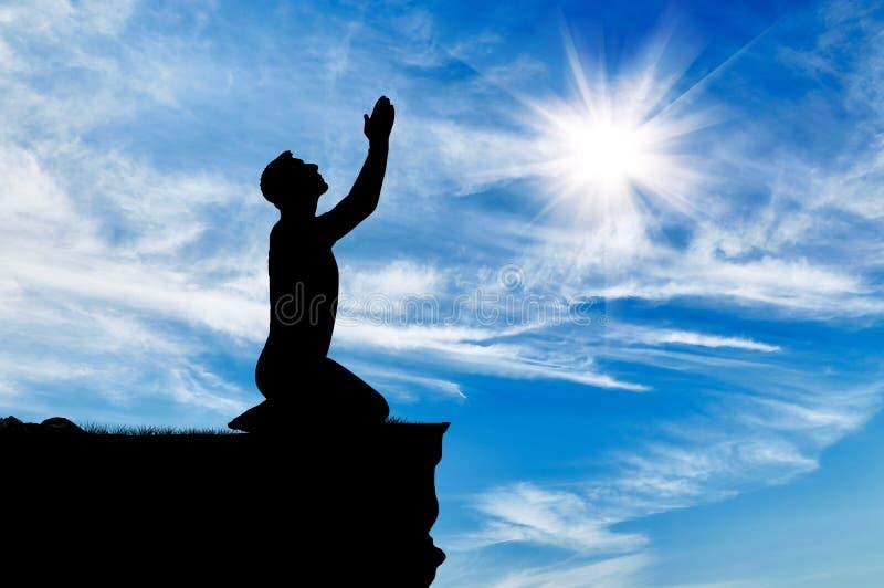 Siluetta di pregare dell'uomo fotografie stock