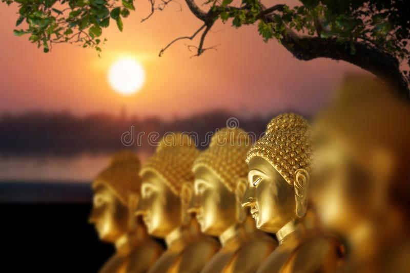 Siluetta di riflessione dell'acqua di Buddha sul tramonto con la montagna essere immagine stock libera da diritti