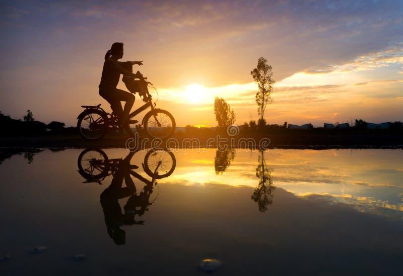 Siluetta di riflessione della madre con il suo bambino sul agai della bicicletta fotografia stock libera da diritti