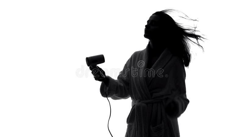 Siluetta di signora graziosa sicura che asciuga col phon i suoi capelli, haircare e bellezza fotografia stock