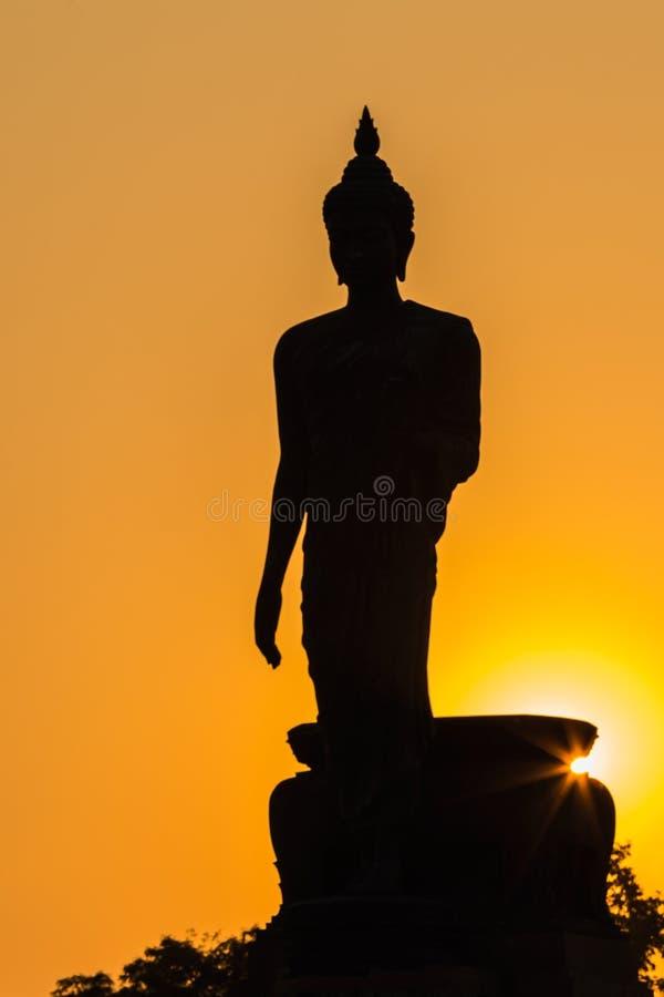 Siluetta di stare la grande statua di Buddha durante il tramonto immagini stock libere da diritti