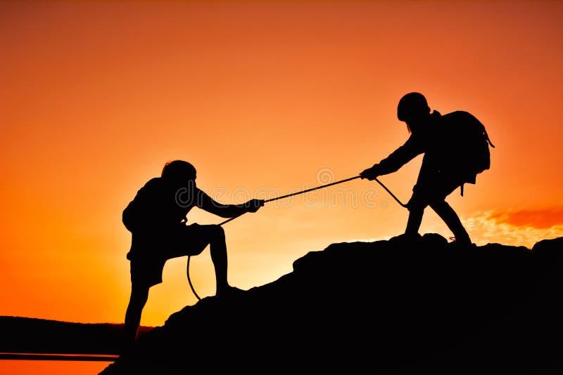 Siluetta di successo d'aiuto di lavoro di squadra dell'uomo della ragazza sulla montagna superiore immagini stock
