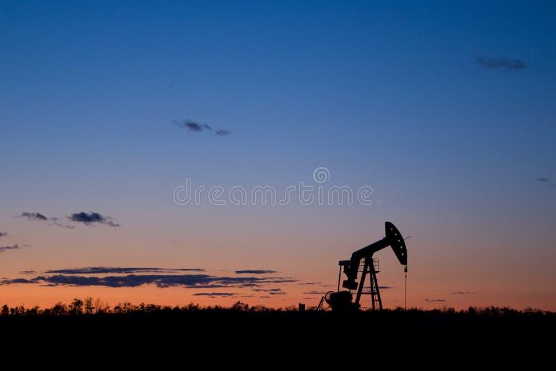 Siluetta di tramonto del pumpjack del pozzo di petrolio immagini stock libere da diritti