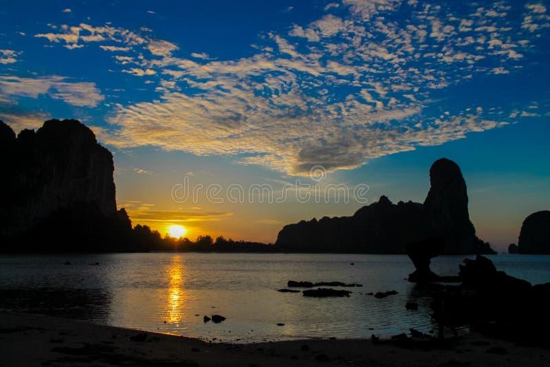 Siluetta di tramonto della scogliera nella baia ey della ferrovia del mare in Tailandia fotografie stock