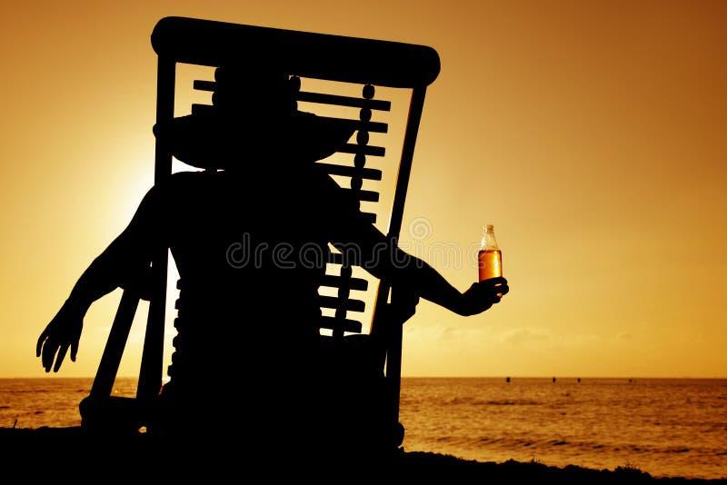 Siluetta di tramonto di Deckchair e della birra immagine stock