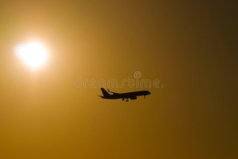 Siluetta di un aereo al tramonto contro lo sfondo di un cielo arancio fotografie stock libere da diritti