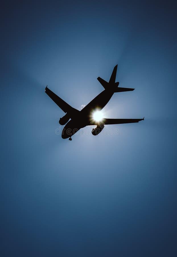 Siluetta di un aeroplano durante l'approccio davanti al sole luminoso fotografia stock libera da diritti