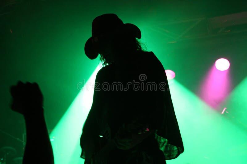 Siluetta di un chitarrista in scena con un cappello da cowboy con il pugno del fan davanti al riflettore verde fotografia stock