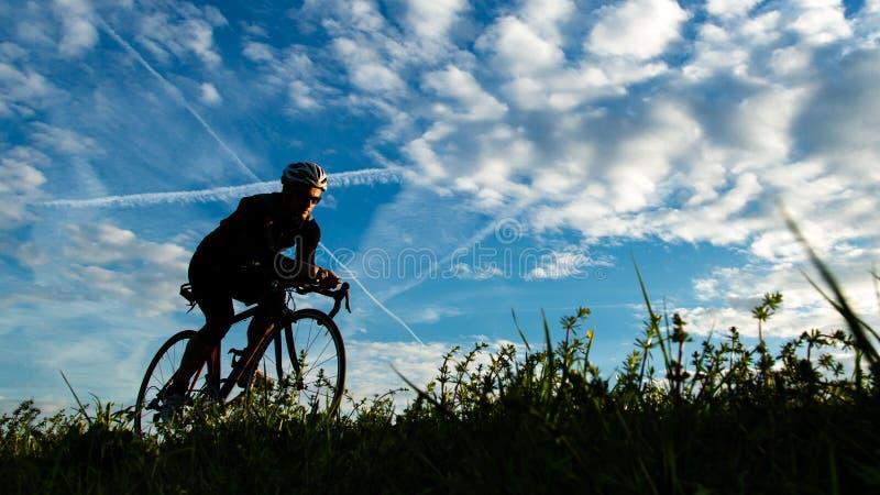 Siluetta di un ciclista fotografie stock
