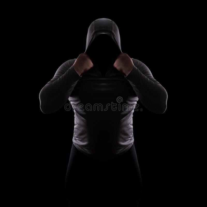 Siluetta di un club maschio di lotta in un cappuccio senza un fronte Siluetta dell'inseguitore su fondo nero, in incognito, anoni fotografia stock