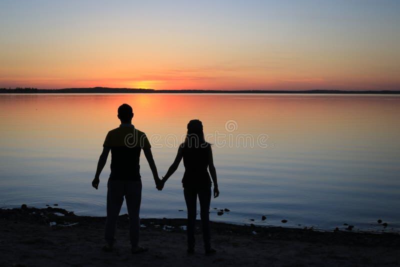 Siluetta di un coupke alla spiaggia nel tramonto immagine stock