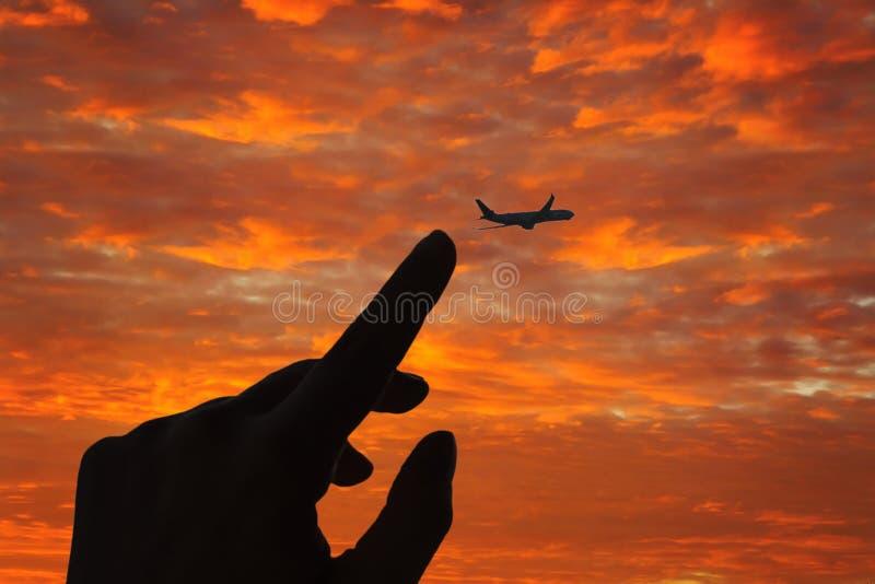 Siluetta di un dito femminile che prova a toccare un aeroplano di volo nel cielo Concetto fotografie stock libere da diritti