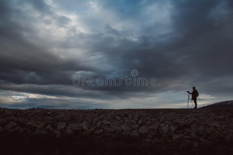 Siluetta di un fotografo o di un viaggiatore con la condizione del treppiede sulla pietra Fondo di un cielo drammatico Funzioname fotografie stock