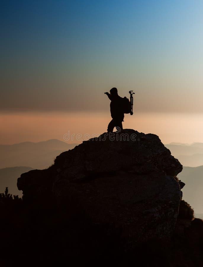 Siluetta di un fotografo sulla cima della montagna fotografie stock