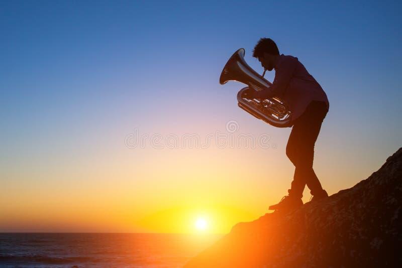Siluetta di un giovane che gioca la tromba sulla costa di mare rocciosa durante il tramonto fotografia stock libera da diritti