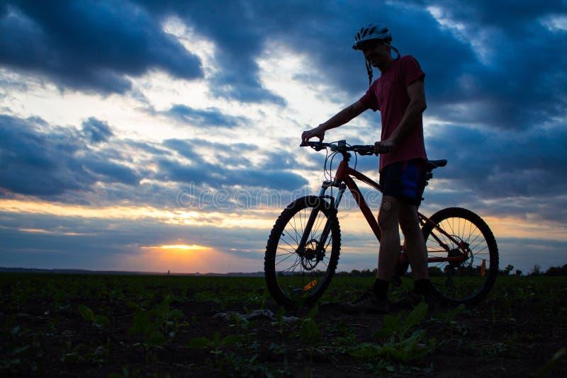 Siluetta di un giovane con una bicicletta nel campo al cielo di tramonto con le nuvole drammatiche immagine stock