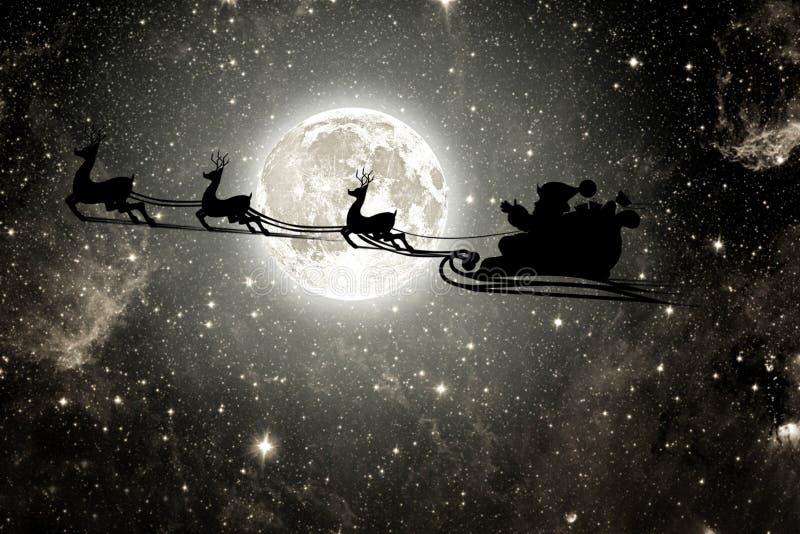 Siluetta di un goth il Babbo Natale di volo contro lo sfondo del cielo notturno fotografie stock