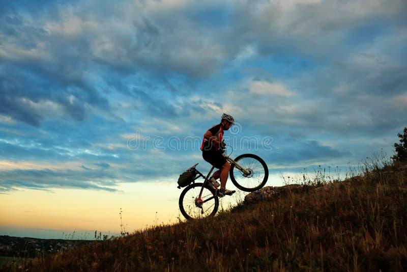Siluetta di un motociclista e di una bicicletta sul cielo fotografia stock