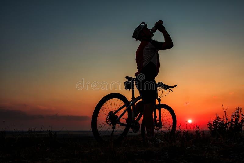 Siluetta di un motociclista e di una bicicletta sul fondo del cielo immagini stock