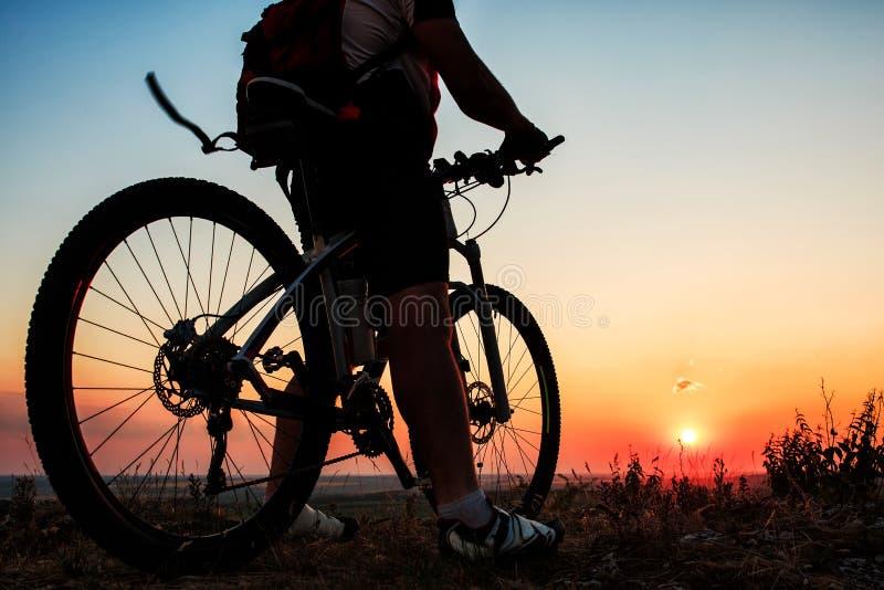 Siluetta di un motociclista e di una bicicletta sul fondo del cielo fotografia stock