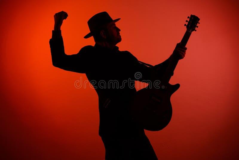 Siluetta di un musicista che gioca strumento in un cappello immagini stock libere da diritti